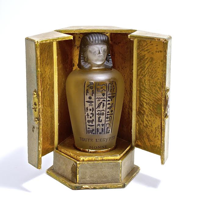 1917 Baccarat, Monne Toute I'Egypte perfume bottle, cover, inner stopper; clear/frost crystal molded  label black patina. Baccarat mark, box 4 1/8 in.
